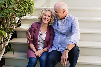 Couple sitting on front doorsteps